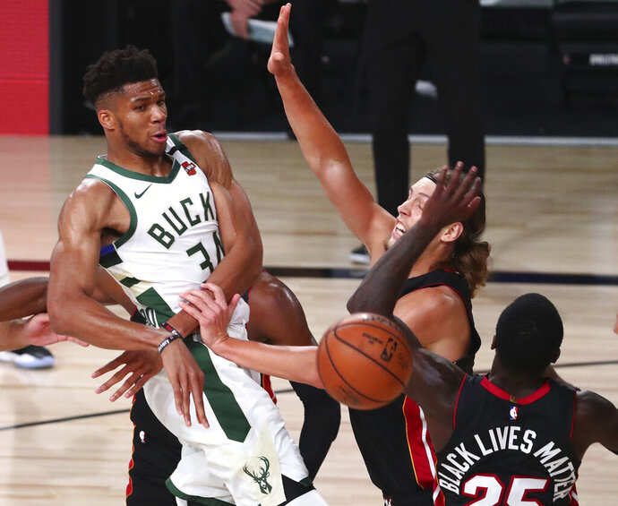 Milwaukee Bucks forward Giannis Antetokounmpo (34) passes the ball against Miami Heat forward Kelly Olynyk (9) and guard Kendrick Nunn (25) during the second half of an NBA basketball game Thursday, Aug. 6, 2020, in Lake Buena Vista, Fla. (Kim Klement/Pool Photo via AP)