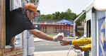Aaron Denison, left, owner of Yuma Snow On The Go, hands a cup of ice water to a U.S. Postal Service carrier who stopped in for a cool refreshment Thursday afternoon, June 17, 2021, in Yuma, Ariz. (Randy Hoeft/The Yuma Sun via AP)