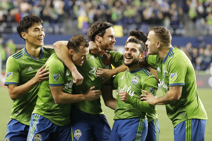 Seattle Sounders midfielder Gustav Svensson, center, celebrates with teammates after he scored a goal against Real Salt Lake during the second half of an MLS Western Conference semifinal playoff soccer match Wednesday, Oct. 23, 2019, in Seattle. The Sounders won 2-0. (AP Photo/Ted S. Warren)