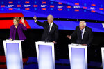 From left, Democratic presidential candidate Sen. Elizabeth Warren, D-Mass., and former Vice President Joe Biden raise their hands as candidate Sen. Bernie Sanders, I-Vt., speaks Tuesday, Jan. 14, 2020, during a Democratic presidential primary debate hosted by CNN and the Des Moines Register in Des Moines, Iowa. (AP Photo/Patrick Semansky)