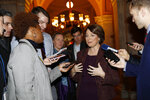 Sen. Amy Klobuchar, D-Minn., center, talks to reporters as she arrives at the Capitol in Washington, Wednesday, Jan. 22, 2020. The U.S. Senate plunges into President Donald Trump's impeachment trial with Republicans abruptly abandoning plans to cram opening arguments into two days but solidly rejecting for now Democratic demands for more witnesses to expose what they deem Trump's