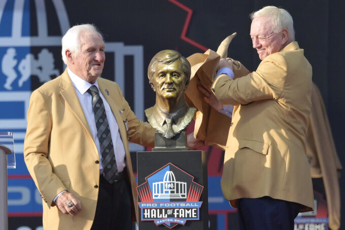 Former NFL football executive Gil Brandt, left, and presenter Jerry Jones, owner of the Dallas Cowboys, unveil the bust of Brandt during the induction ceremony at the Pro Football Hall of Fame, Saturday, Aug. 3, 2019, in Canton, Ohio. (AP Photo/David Richard)