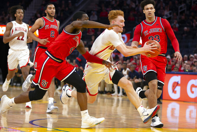 Arizona guard Nico Mannion (1) drives to the basket between St. John's guard Greg Williams Jr. (4) and forward Ian Steere (33) during the second half of an NCAA college basketball game Saturday, Dec. 21, 2019, in San Francisco. (AP Photo/D. Ross Cameron)