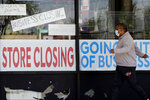 A man looks at signs of a closed store due to COVID-19 in Niles, Ill., Thursday, May 21, 2020. More than 2.4 million people applied for U.S. unemployment benefits last week in the latest wave of layoffs from the viral outbreak that triggered widespread business shutdowns two months ago and sent to economy into a deep recession. (AP Photo/Nam Y. Huh)