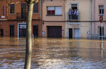 People stand at a balcony during flooding following a storm in Girona, Spain, on Thursday, Jan. 23, 2020. At least 11 have died and five people remained missing on Thursday following a calamitous storm that has caused rivers to overflow and sea waters to inundate vast agricultural areas in eastern Spain. (AP Photo/Emilio Morenatti)