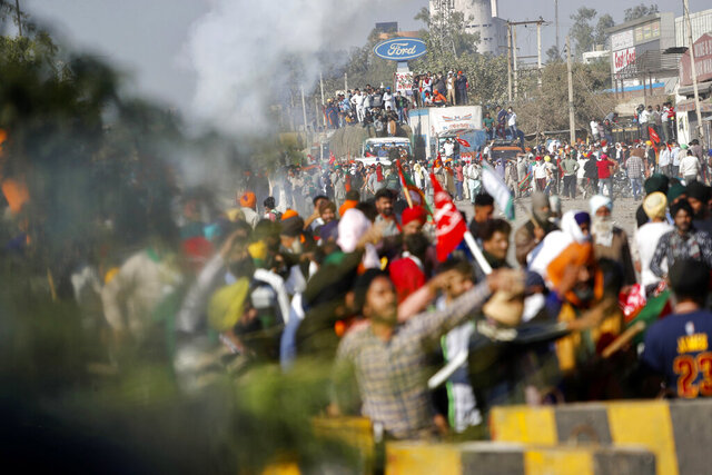 Protesting farmers shout slogans and face security officers at the border between Delhi and Haryana state, Friday, Nov. 27, 2020. Thousands of agitating farmers in India faced tear gas and baton charge from police on Friday after they resumed their march to the capital against new farming laws that they fear will give more power to corporations and reduce their earnings. While trying to march towards New Delhi, the farmers, using their tractors, cleared concrete blockades, walls of shipping containers and horizontally parked trucks after police had set them up as barricades and dug trenches on highways to block roads leading to the capital. (AP Photo/Manish Swarup)