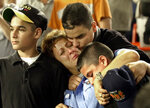 FILE - In this Friday, Sept. 21, 2001 file photo, Carol Gies, center, a wife of a missing firefighter, leans on son Ronnie as she is consoled by sons Bobbie, right, and Tommy, behind, during the ceremonies for the victims of the World Trade Center prior to the New York Mets game against the Atlanta Braves at Shea Stadium in New York. (AP Photo/Bill Kostroun, File)