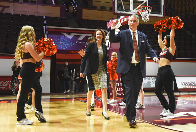 New Virginia Tech men's NCAA college basketball head coach Mike Young and his wife, Margaret gesture in Blacksburg, Va., Monday, April 8, 2019. (Michael Shroyer/The Roanoke Times via AP)