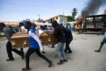 In this Tuesday, Nov. 19, 2019 photo, protesters carry a coffin that contain the remains of a protester, while a vehicle burns in the background, in Port-au-Prince, Haiti. Hundreds of people attended the funerals for five people killed during anti-government protests, three of whom were allegedly shot by police while participating in the protests. (AP Photo/Dieu Nalio Chery)