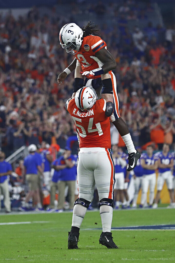 Virginia  offensive tackle Ryan Nelson (54) lifts quarterback Bryce Perkins (3) as they celebrate a score during the Orange Bowl NCAA college football game against Florida, Monday, Dec. 30, 2019, in Miami Gardens, Fla. (Erin Edgerton/The Daily Progress via AP)