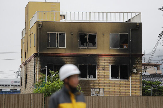 A security guard stands near the Kyoto Animation Studio building destroyed in an attack, Friday, July 19, 2019, in Kyoto, Japan. A man screaming