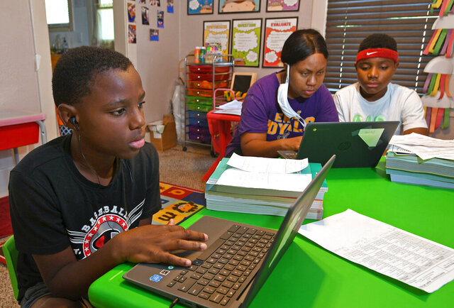 From left: Michael Henry, 11; his mother Mary Euell, 30; and his brother Mario Henry, 12, work through math lessons remotely at their west Erie, Pa., home, Tuesday, Sept. 8, 2020, on the first day of classes for the Erie School District. Most of the district's 11,000 students are beginning the school year with remote learning, to slow the spread of COVID-19, the new coronavirus. (Christopher Millette/Erie Times-News via AP)