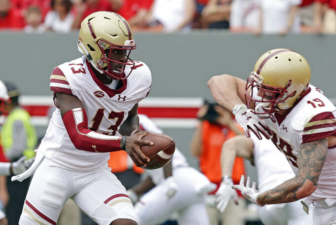 Boston College quarterback Anthony Brown (13) hands off to Ben Glines (19) during the first half an NCAA college football game against North Carolina State in Raleigh, N.C., Saturday, Oct. 6, 2018. (AP Photo/Gerry Broome)