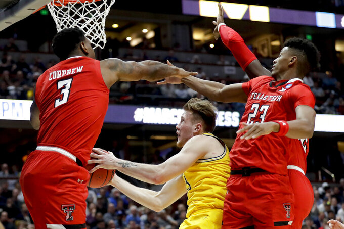 Michigan forward Ignas Brazdeikis, middle, drives to the basket between Texas Tech forward Deshawn Corprew, let, and guard Jarrett Culver during the first half an NCAA men's college basketball tournament West Region semifinal Thursday, March 28, 2019, in Anaheim, Calif. (AP Photo/Marcio Jose Sanchez)