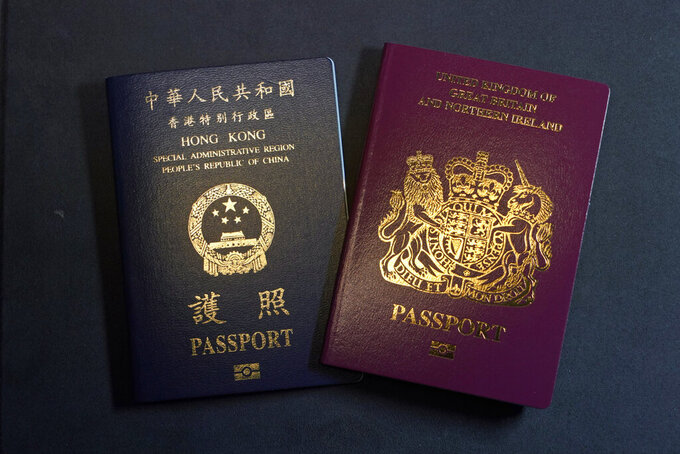 FILE- In this Friday, Jan. 29, 2021 file photo, a British National Overseas passports (BNO) and a Hong Kong Special Administrative Region of the People's Republic of China passport are pictured in Hong Kong. The British government said Thursday, April 8, 2021, it is setting up a 43 million pound ($59 million) fund to help migrants from Hong Kong settle in the country as they escape increasing political repression in the former colony.(AP Photo/Kin Cheung, File)