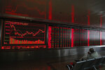 An investor sits near an electronic board displaying stock prices at a brokerage house in Beijing, Wednesday, Oct. 16, 2019. Asian shares were higher Wednesday after a gain on Wall Street boosted by healthy earnings reports from U.S. companies. (AP Photo/Andy Wong)