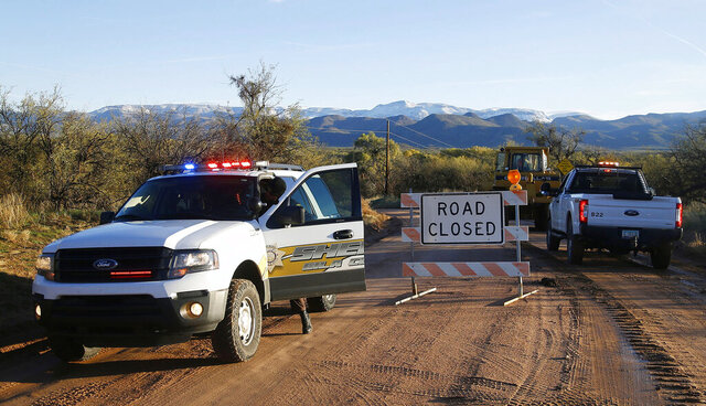 FILE - This Saturday, Nov. 30, 2019, file photo shows the road closed near Bar X road and Tonto Creek after a vehicle was washed by flood waters in Tonto Basin, Ariz. Authorities in rural Arizona recovered a body Friday, Dec. 13, 2019, that they believe is a 6-year-old girl swept away two weeks ago when her family tried to cross surging creek waters. The body was found in Roosevelt Lake about 20 miles (32 kilometers) south of Tonto Basin, where Willa Rawlings initially went missing, according to a news release from Sheriff J. Adam Shepherd. The announcement from Gila County sheriff's officials came on the same day as family members held funeral services for Willa Rawlings and her brother Colby, 5. (Patrick Breen/The Arizona Republic via AP,File)