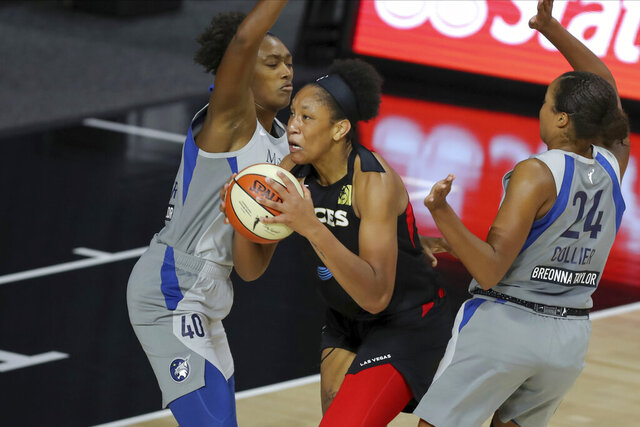 Las Vegas Aces' A'ja Wilson drives between Minnesota Lynx's Kayla Alexander (40) and Napheesa Collier during the first half of a WNBA basketball game Thursday, Aug. 13, 2020, in Bradenton, Fla. (AP Photo/Mike Carlson)