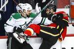 Dallas Stars' Jamie Benn, left, checks Calgary Flames' Sean Monahan during the first period of an NHL hockey game Wednesday, Nov. 13, 2019, in Calgary, Alberta. (Jeff McIntosh/The Canadian Press via AP)