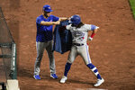 Toronto Blue Jays' Bo Bichette, right, is helped to put on a blazer by pitcher Jose Berrios after hitting a two-run home run off Baltimore Orioles starting pitcher Keegan Akin during the seventh inning of the second game of a baseball doubleheader, Saturday, Sept. 11, 2021, in Baltimore. (AP Photo/Julio Cortez)