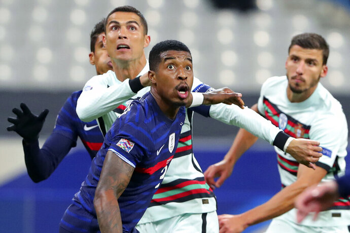 FILE - In this Sunday, Oct. 11, 2020 file photo Portugal's Cristiano Ronaldo, left, and France's Presnel Kimpembe, centre, eye the ball, during the UEFA Nations League soccer match between France and Portugal at the Stade de France in Saint-Denis, north of Paris, France. The Portuguese soccer federation says Cristiano Ronaldo has tested positive for the coronavirus. The federation says Ronaldo is doing well and has no symptoms. He has been dropped from the country's Nations League match against Sweden on Wednesday, Oct. 14. (AP Photo/Thibault Camus, File)