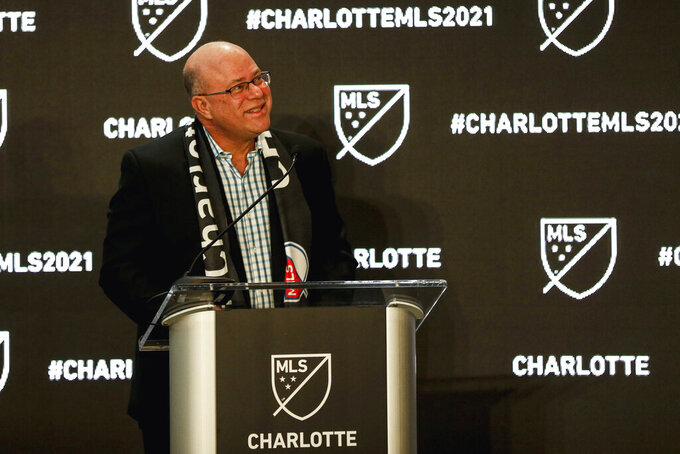 David Tepper looks up at fans as he announces he will bring an MLS soccer team to Charlotte in 2021 at an event in Charlotte, N.C., Tuesday, Dec. 17, 2019. (AP Photo/Nell Redmond