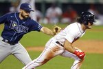 Tampa Bay Rays' Brandon Lowe tags Boston Red Sox's Andrew Benintendi on a run down at third base during the eighth inning of a baseball game, Tuesday, Aug. 11, 2020, in Boston. (AP Photo/Michael Dwyer)
