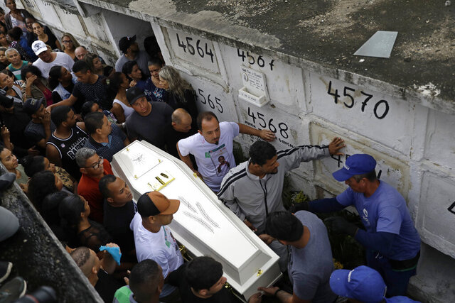 FILE - In this Sept. 22, 2019 file photo, people carry the coffin of Agatha Sales Felix, who was hit by a a stray bullet, at a cemetery in Rio de Janeiro, Brazil. Police eventually announced that it was an officer who fired the shot that killed the 8-year-old girl. (AP Photo/Silvia Izquierdo, File)