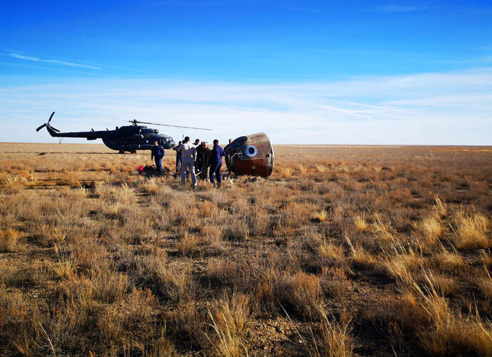 In this photo provided by Russian Defense Ministry Press Service, the rescue team gather next to the Soyuz MS-10 space capsule after it made an emergency landing in a field about 20 km (12,43 miles) Dzhezkazgan, about 450 kilometers (280 miles) northeast of Baikonur, Kazakhstan, Thursday, Oct. 11, 2018. NASA astronaut Nick Hague and Roscosmos' Alexei Ovchinin lifted off as scheduled at 2:40 p.m. (0840 GMT; 4:40 a.m. EDT) Thursday from the Russian-leased Baikonur cosmodrome in Kazakhstan, but their Soyuz booster rocket failed about two minutes after the launch. (Russian Defense Ministry Press Service photo via AP)