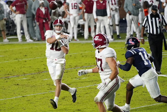 Alabama quarterback Mac Jones (10) throws a 3-yard touchdown pass to tight end Miller Forristall (87) as Mississippi linebacker Daylen Gill (14) defends during the second half of an NCAA college football game in Oxford, Miss., Saturday, Oct. 10, 2020. Alabama won 63-48. (AP Photo/Rogelio V. Solis)