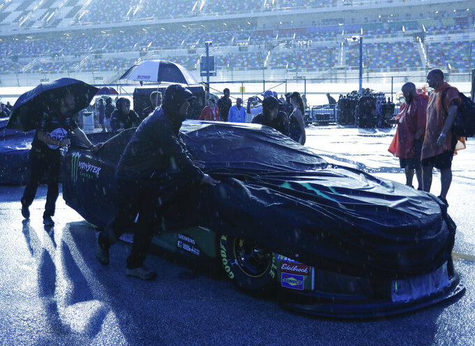 Kurt Busch's crew pushes his car back to the garage after a NASCAR Cup Series auto race was cancelled because of rain at Daytona International Speedway, Saturday, July 6, 2019, in Daytona Beach, Fla. The race was rescheduled for Sunday. (AP Photo/Terry Renna)