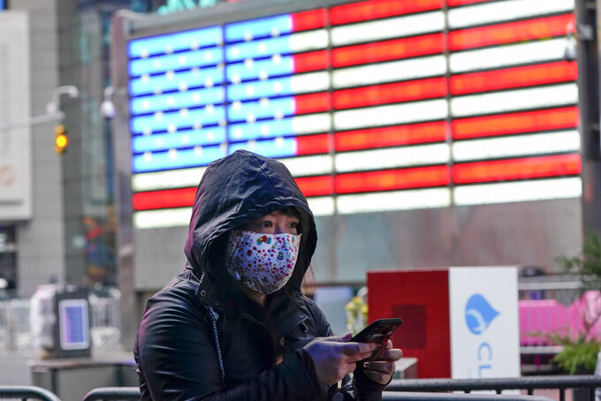 A woman wears a protective mask during the coronavirus pandemic in Times Square Thursday, Dec. 31, 2020, in New York. (AP Photo/Frank Franklin II)