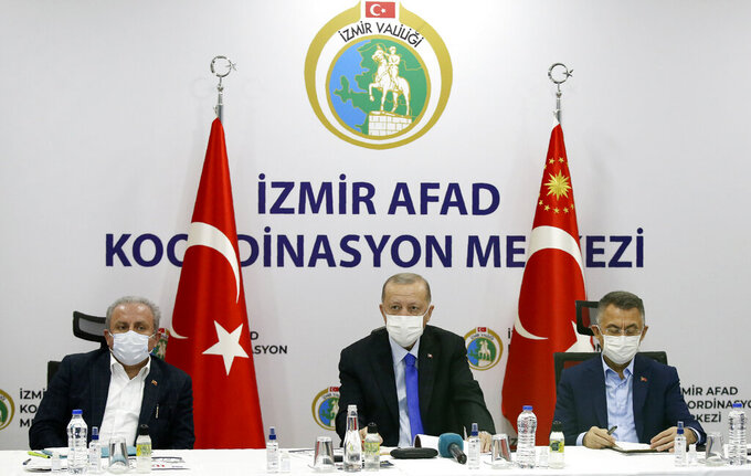 Turkey's President Recep Tayyip Erdogan, centre, flanked by his deputy Fuat Oktay, right, and Parliament Speaker Mustafa Sentop, speaks at Izmir AFAD emergency response center, in Izmir, Turkey, Saturday, Oct. 31, 2020. Three young children and their mother were rescued alive from the rubble of a collapsed building in western Turkey on Saturday, some 23 hours after a powerful earthquake in the Aegean Sea killed several people and injured more than 800 others.(Turkish Presidency via AP, Pool)