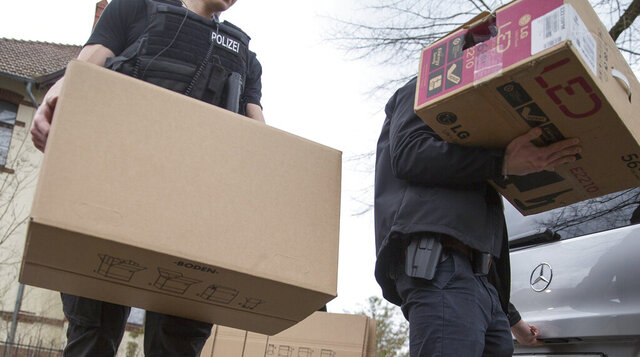 Police officers carrying boxes out of a house after an apartment raid in Berlin, Germany, Thursday, March 18, 2020. After the ban of the Reich Citizens' Group