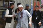 An injured man talks on his mobile phone after an explosion in Kabul, Afghanistan, Wednesday, May 8, 2019. The Taliban attacked the offices of an international NGO called Counterpart International, in the Afghan capital, setting off a huge explosion and battling Afghan security forces in an assault that wounded at least nine people, officials said. (AP Photo/Rahmat Gul)