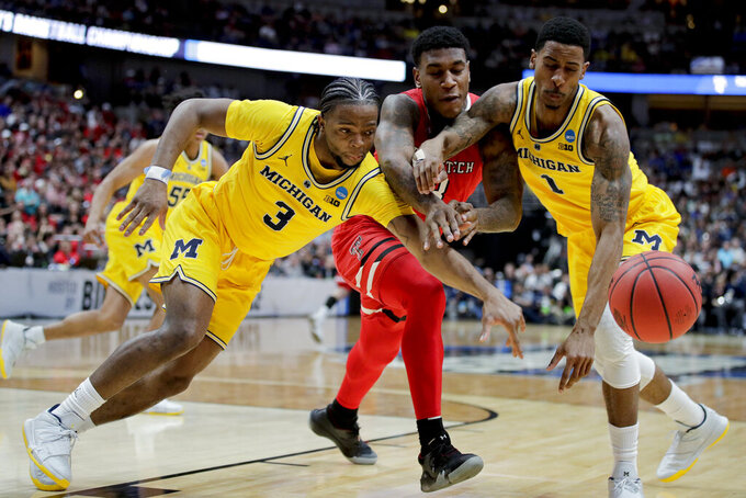 Texas Tech forward Deshawn Corprew, middle, reaches for a loose ball between Michigan guard Zavier Simpson, left, and guard Charles Matthews during the first half an NCAA men's college basketball tournament West Region semifinal Thursday, March 28, 2019, in Anaheim, Calif. (AP Photo/Jae C. Hong)