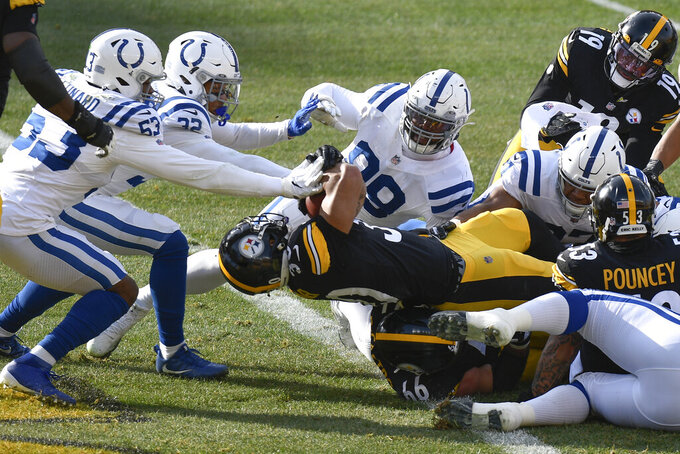 Pittsburgh Steelers running back James Conner (30) twists over the goal line for a touchdown as Indianapolis Colts defensive tackle DeForest Buckner (99), outside linebacker Darius Leonard (53) and free safety Julian Blackmon (32) defend during the first half of an NFL football game, Sunday, Dec. 27, 2020, in Pittsburgh. (AP Photo/Don Wright)