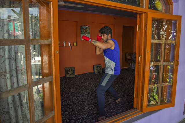 Kashmiri boxer Eyed Akeel Khan practices inside his house in Srinagar, Indian controlled Kashmir, April 23, 2020. Like many other athletes, the coronavirus pandemic has restricted Khan to his home. But lockdown for the 7 million residents of Kashmir is nothing new and the ongoing restrictions due to the pandemic is not the first time he has had to practice his sport at home. (AP Photo/Dar Yasin)