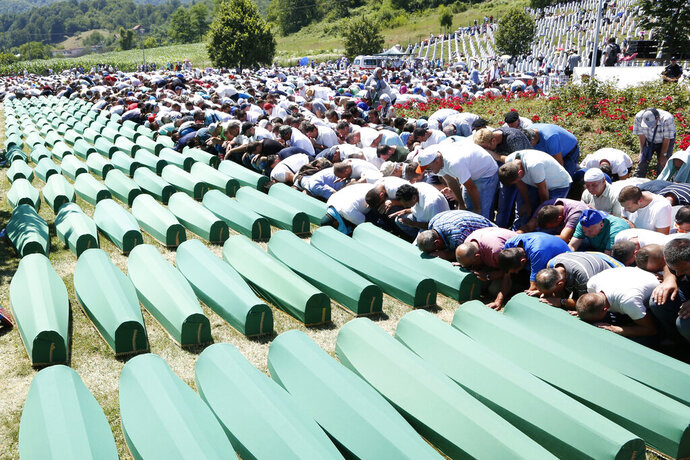 FILE - A Monday, July 11, 2016 file photo of Bosnian people saying prayers in front of coffins during a funeral ceremony for the 127 victims at the Potocari memorial complex near Srebrenica, 150 kilometers (94 miles) northeast of Sarajevo, Bosnia and Herzegovina. A Bosnian Serb leader has wrongly called the 1995 Srebrenica massacre, where over 8,000 Muslim men and boys were killed by Bosnian Serb troops,