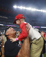 Atlanta Braves manager Brian Snitker hoists his grandson Luke while celebrating after the team clinched the NL East title with a 6-0 victory over the San Francisco Giants in a baseball game Friday, Sept. 20, 2019, in Atlanta. (Curtis Compton/Atlanta Journal Constitution via AP)