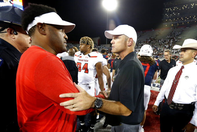 Arizona head coach Kevin Sumlin, left, and Texas Tech head coach Matt Wells meet at midfield following an NCAA college football game, Saturday, Sept. 14, 2019, in Tucson, Ariz. Arizona defeated Texas Tech 28-14. (AP Photo/Ralph Freso)