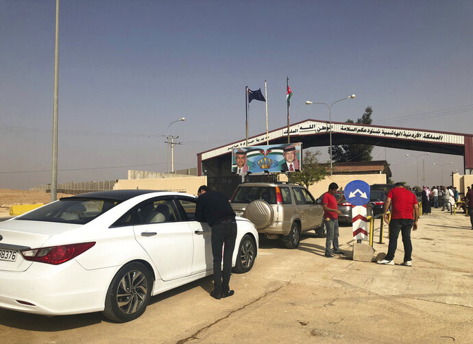 Jordanian cars prepare to cross into Syria, at the Jordanian-Syrian border Jaber crossing point, in Mafraq, Jordan, Monday, Oct. 15, 2018.  A vital border crossing linking Syria and Jordan has reopened for the first time in three years, promising to restore commercial trade and travel between the two countries. (AP Photo/Omar Akour)