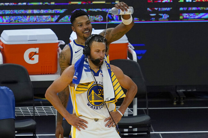 Golden State Warriors forward Kent Bazemore, top, pours water on the head of guard Stephen Curry after an NBA basketball game against the Memphis Grizzlies in San Francisco, Sunday, May 16, 2021. (AP Photo/Jeff Chiu)