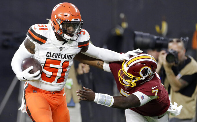 FILE - In this Thursday, Aug. 8, 2019 file photo, Cleveland Browns linebacker Mack Wilson (51) returns an interception for a touchdown, as Washington Redskins quarterback Dwayne Haskins (7) reaches for him during the first half of an NFL preseason football game in Cleveland. Proficient on social media, Browns rookie linebacker Mack Wilson has also shown a nose for the ball. The fifth-round pick from Alabama had two interceptions in his NFL preseason debut and has been impressive in camp. (AP Photo/Ron Schwane, File)