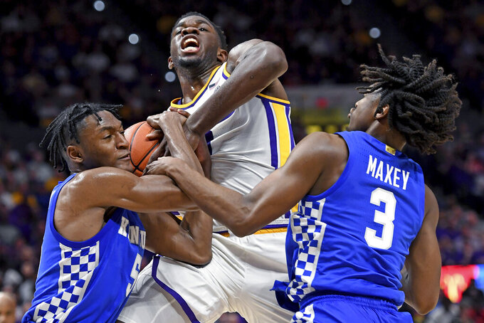 Kentucky guard Immanuel Quickley (5), LSU forward Darius Days, center, and Kentucky guard Tyrese Maxey (3) have a hand on the ball as Days was driving to the basket during the first half of an NCAA college basketball game, Tuesday, Feb. 18, 2020, in Baton Rouge, La. (AP Photo/Bill Feig)