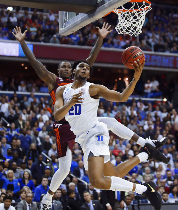Duke center Marques Bolden (20) drive past Virginia Tech guard Ty Outlaw (42) to score during the second half of an NCAA men's college basketball tournament East Region semifinal in Washington, Friday, March 29, 2019. Duke won 75-73. (AP Photo/Alex Brandon)