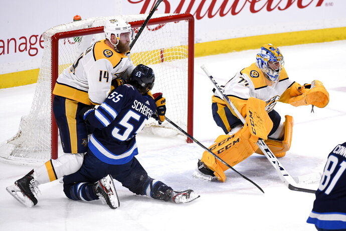 Winnipeg Jets' Mark Scheifele (55) runs into Nashville Predators' Mattias Ekholm (14) in front of Predators goaltender Juuse Saros (74) during first-period NHL hockey game action in Winnipeg, Manitoba, Sunday Jan. 12, 2020. (Fred Greenslade/The Canadian Press via AP)