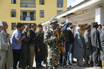 An Indian paramilitary soldier stands guard as Kashmiri voters wait in a queue to cast their votes outside a polling station during the second phase of India's general elections, on the outskirts of Srinagar, Indian controlled Kashmir, Thursday, April 18, 2019. Kashmiri separatist leaders who challenge India's sovereignty over the disputed region have called for a boycott of the vote. Most polling stations in Srinagar and Budgam areas of Kashmir looked deserted in the morning with more armed police, paramilitary soldiers and election staff present than voters. (AP Photo/Mukhtar Khan)