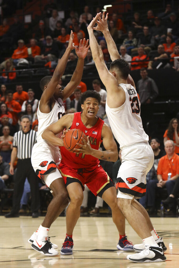 Arizona's Ira Lee (11) fights through Oregon State's Alfred Hollins (4), left, and Gligorije Rakocevic (23), right, during the first half of an NCAA college basketball game in Corvallis, Ore., Thursday, Feb. 28, 2019. (AP Photo/Amanda Loman)