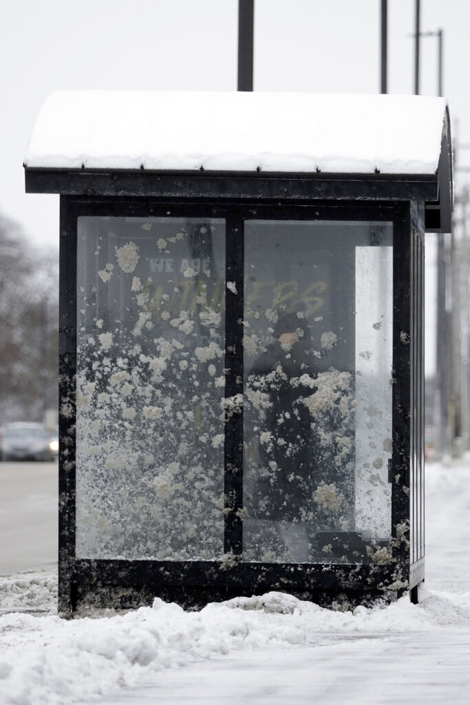 A pedestrian waits for a bus at a stop in Prospect Heights, Ill., Thursday, Feb. 13, 2020. Temps are falling into single digits in the evening and bottom- out at zero or below early Friday. (AP Photo/Nam Y. Huh)